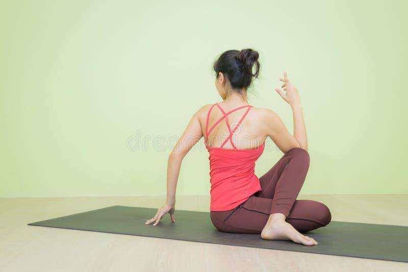 供以座位的转弯瑜伽姿势的妇女 免版税库存图片