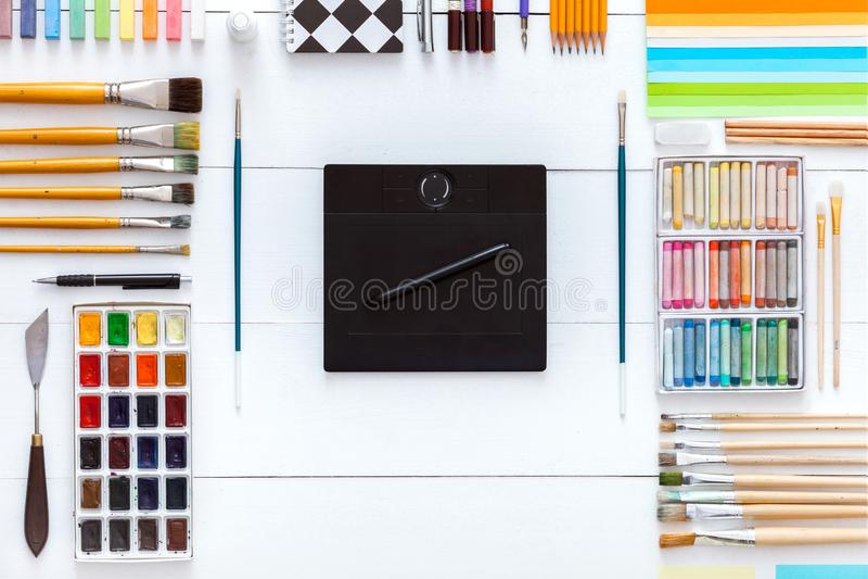 供应和设备创造性的书刊上的图片概念、供应集合和数字wacom片剂的在白色木背景,油漆刷 免版税库存照片