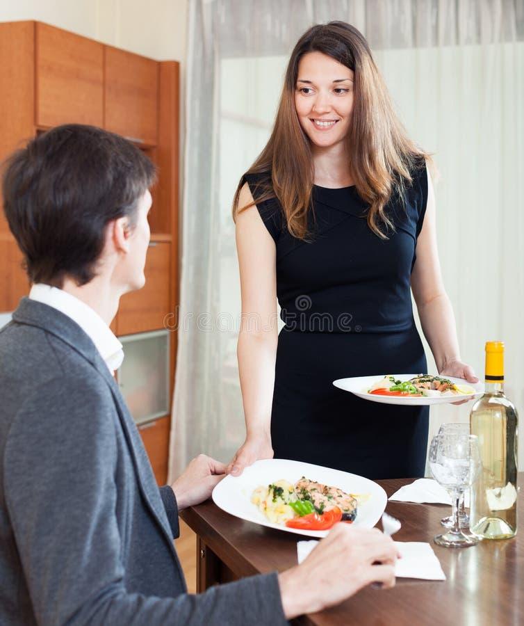供应她的男朋友浪漫晚餐的女孩 免版税库存图片
