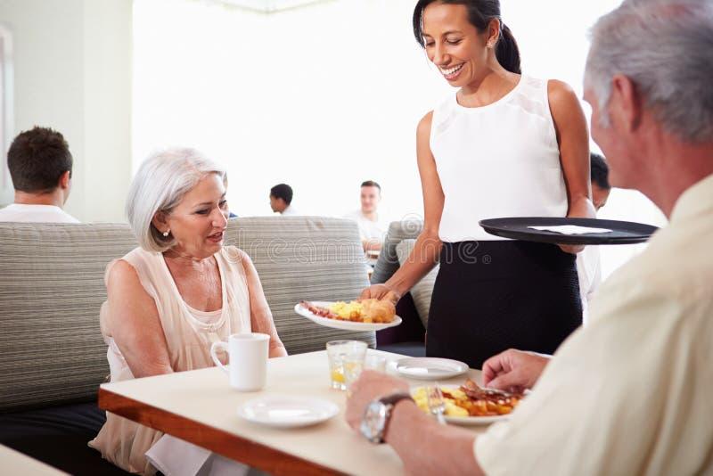 供应资深夫妇早餐的女服务员在旅馆餐馆 免版税库存图片