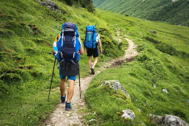 供徒步旅行的小道在Svaneti地区,乔治亚 在艰苦跋涉的两个远足者人步行在山 有背包远足的游人在高地 免版税库存照片