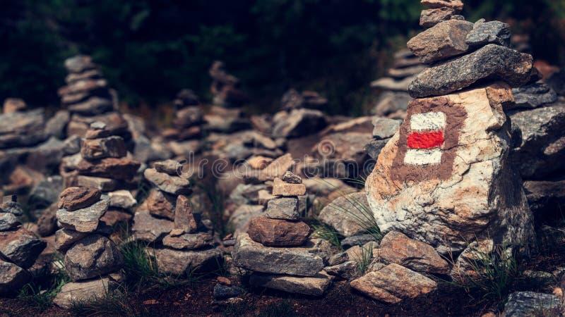 供徒步旅行的小道标志在堆的一个岩石指示绘禅宗石头 道路主导的低谷美丽的漂泊森林国家公园 免版税库存图片
