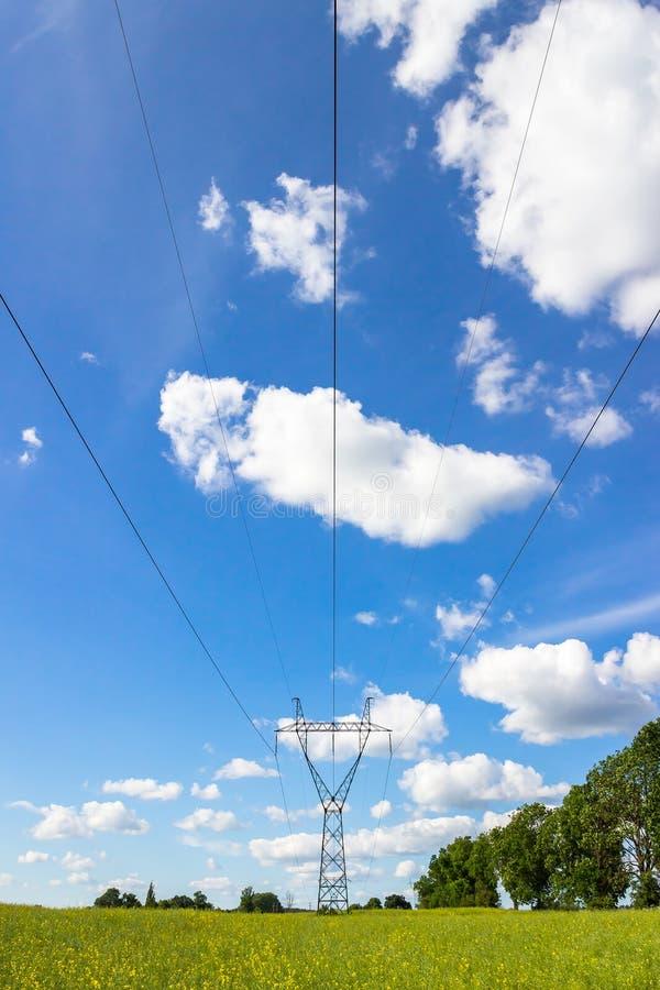 供给定向塔和高压线动力在绿草领域机智 库存照片