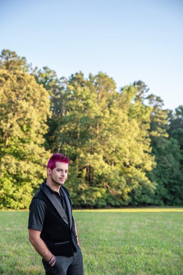 供选择的不同的男性-黑色衣服,傻笑在照相机的桃红色头发 免版税库存图片