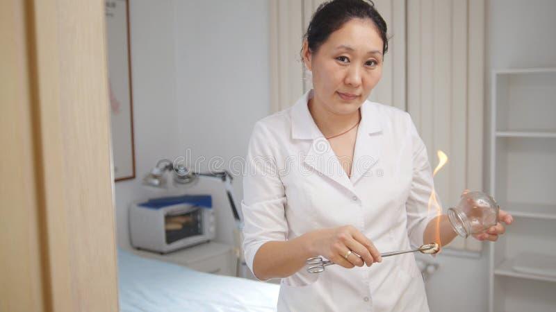 供选择的亚洲西藏医学,医生准备一个玻璃瓶子 图库摄影