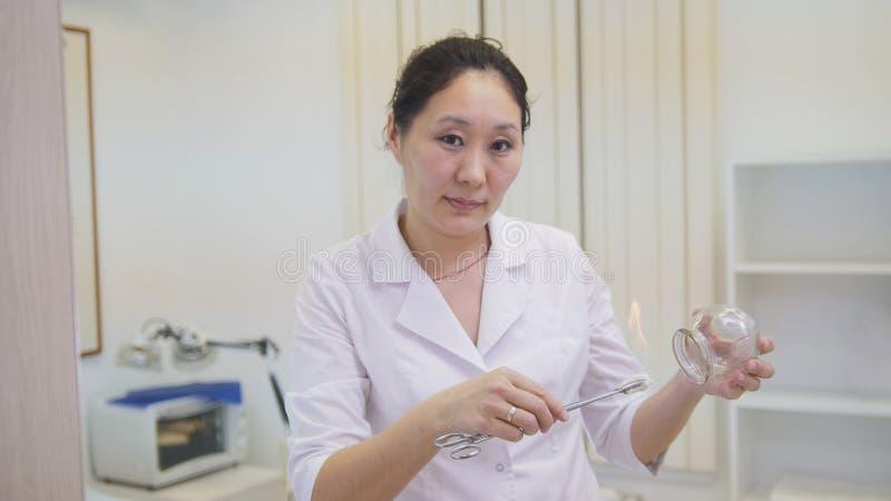 供选择的亚洲西藏医学,医生准备一个玻璃瓶子 库存照片