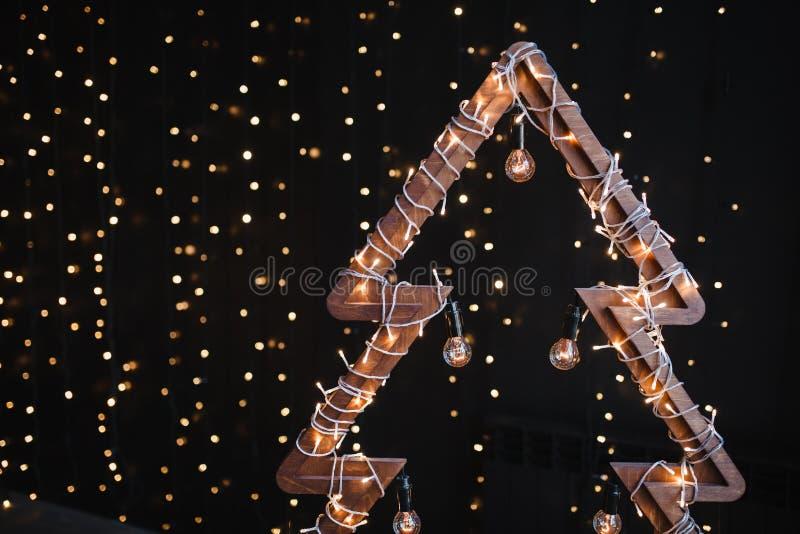 供选择的木圣诞树 与电灯泡的一棵手工制造新年树在诗歌选光黑背景 库存图片