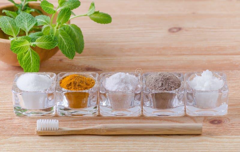 供选择的自然牙膏木糖醇或苏打、姜黄-姜黄,喜马拉雅盐、黏土或者灰、椰子油和木头牙刷, 图库摄影