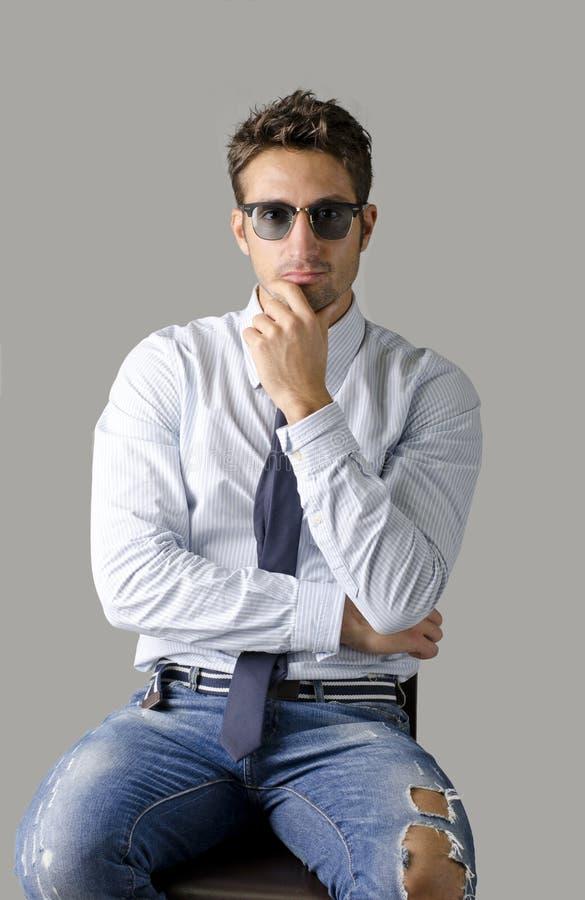 供选择的年轻商人佩带的衬衣、领带和被剥去的牛仔裤 库存图片