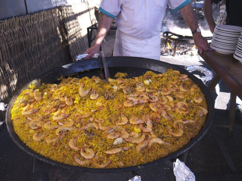 供食一个巨大的平底锅在布里亚纳的肉菜饭在内尔哈安达卢西亚西班牙靠岸 免版税图库摄影