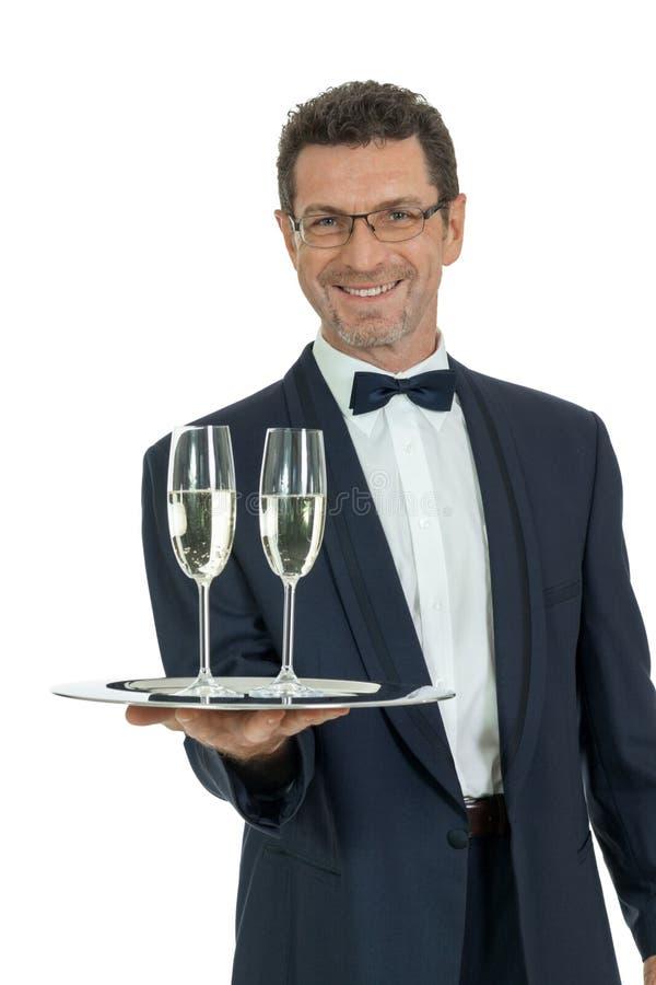 供食两杯香槟的成年男性侍者被隔绝 免版税库存照片