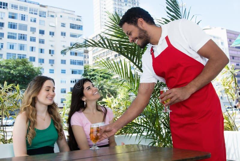 供食冰镇啤酒的笑的侍者对客人 库存图片