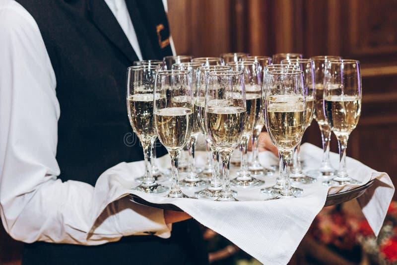 供食在玻璃的侍者时髦的金黄香槟在盘子 Eleg 免版税库存照片