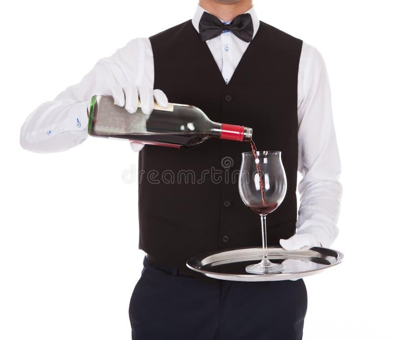 供食在玻璃的侍者红葡萄酒 免版税库存照片