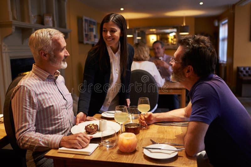 供食点心的女服务员对一对男性夫妇在餐馆 免版税库存照片