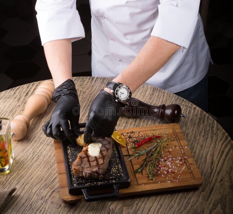供食烤牛排的黑手套的厨师 库存照片