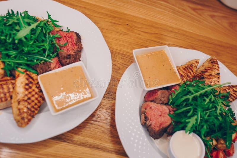 供食热的烤串鸡牛肉内圆角肉用新鲜的芝麻菜圆白菜沙拉的侍者用芥末在餐馆,关闭 库存照片