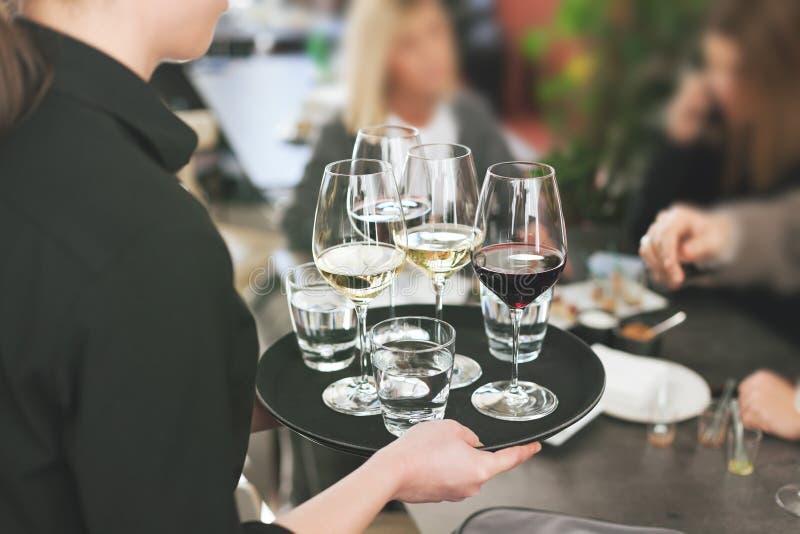 供食白色和红葡萄酒的餐馆的女服务员 免版税图库摄影