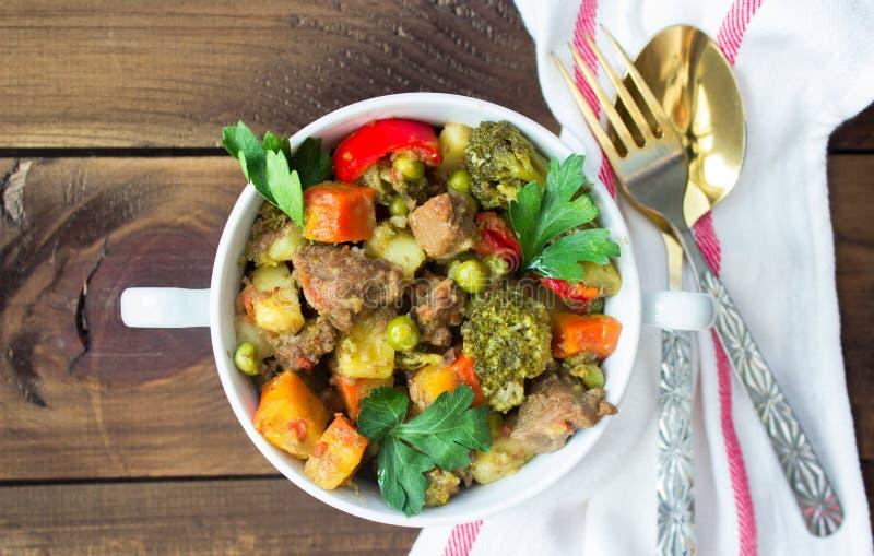 供食的牛肉肉炖了与在陶瓷罐的菜在木背景 免版税图库摄影
