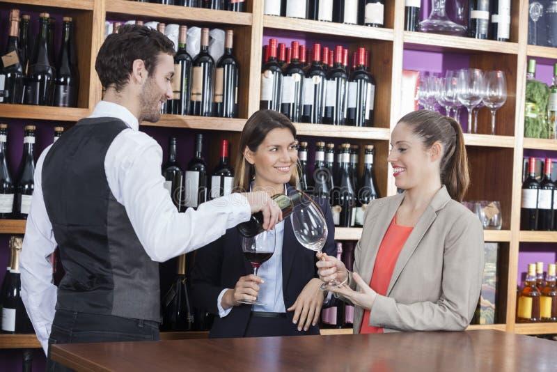 供食红葡萄酒的侍酒者对女性顾客 免版税图库摄影