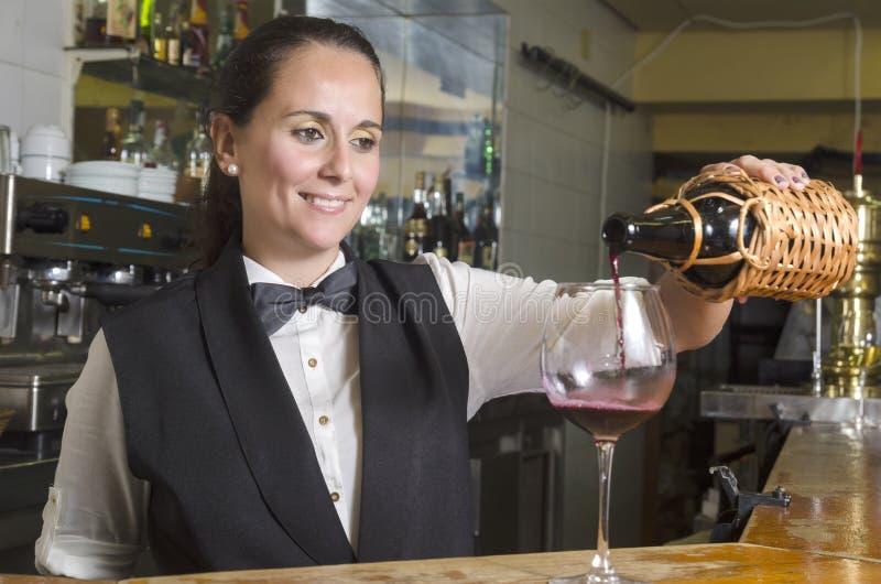 供食红葡萄酒的女服务员 库存图片