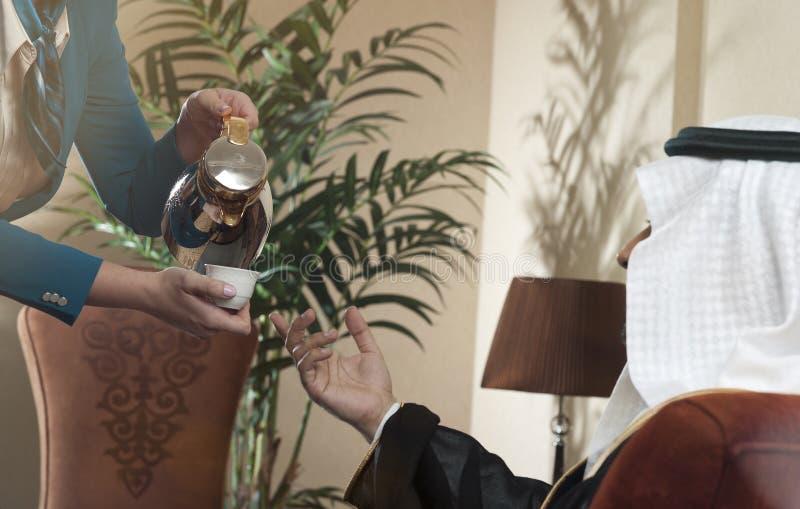 供食阿拉伯咖啡的女服务员对一个富裕的阿拉伯人 免版税库存照片