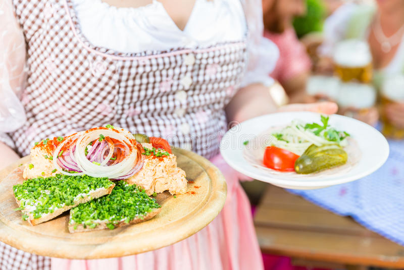 供食巴法力亚食物的女服务员在啤酒庭院里 免版税库存图片