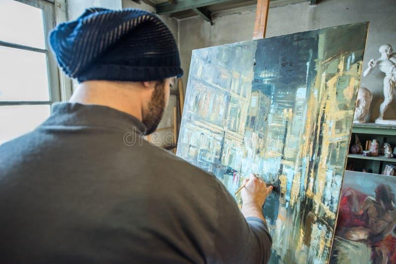 供以人员与刷子在帆布-山水画的绘画 免版税图库摄影