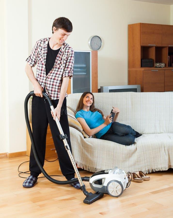供以人员与吸尘器的清洁,当说谎与eBook时的妻子 免版税库存照片