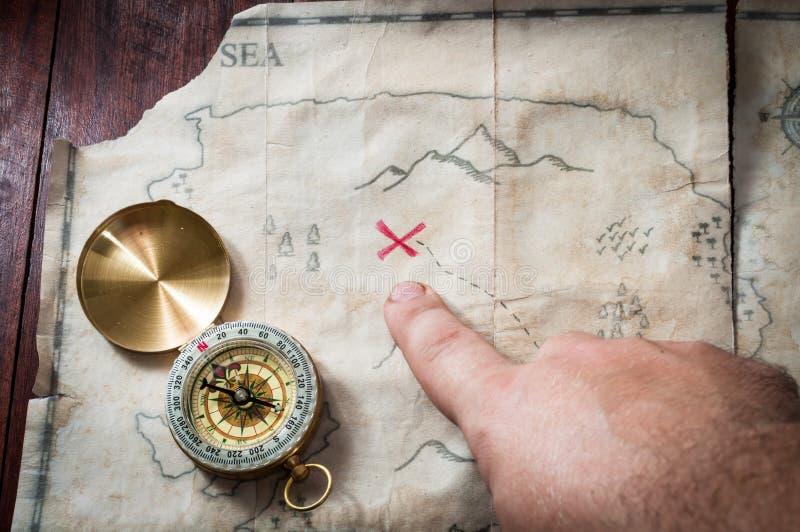 供以人员与手指的点入在古老珍宝地图的红十字与在木书桌上的指南针 库存图片