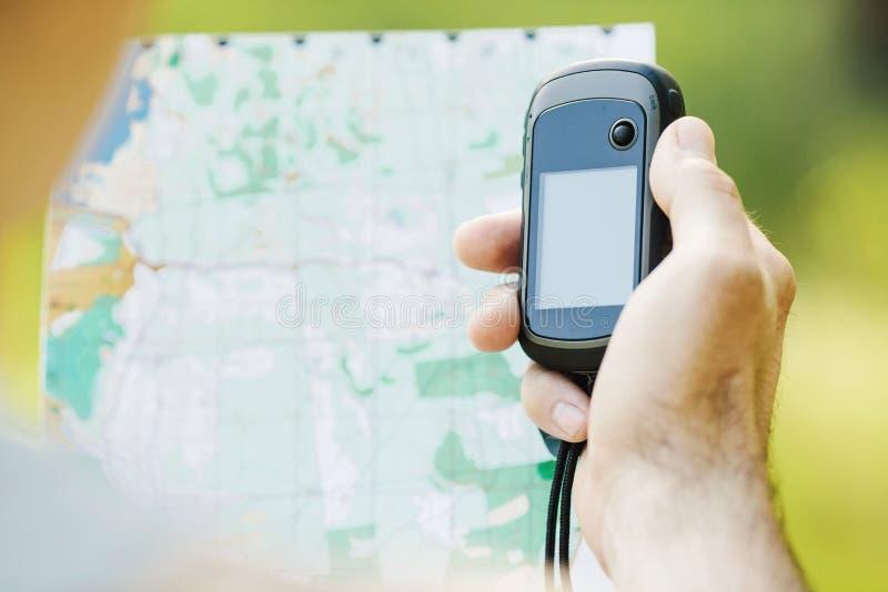 供以人员举行一台GPS接收器和计划在他的手上 免版税库存照片