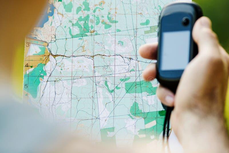 供以人员举行一台GPS接收器和计划在他的手上 免版税库存图片