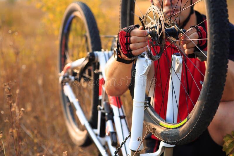供以人员修理自行车的骑自行车者反对绿色自然 免版税库存图片
