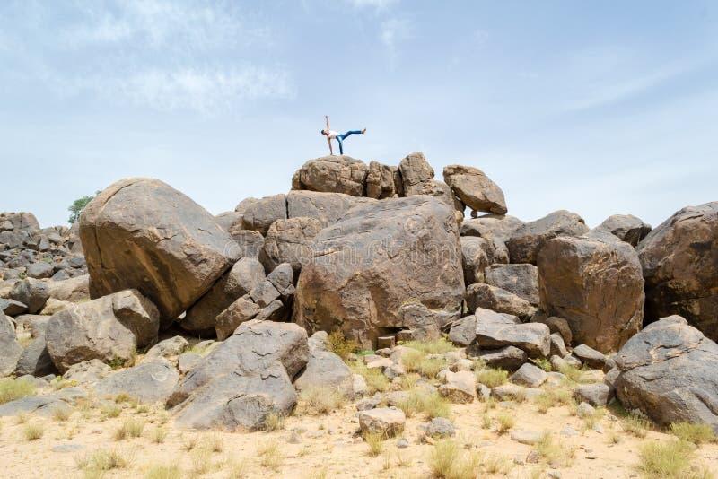 供以人员做在岩石#2的杂技运动 免版税库存照片