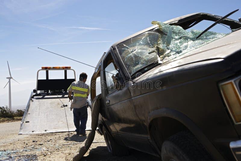 供以人员准备举在拖车上的被碰撞的汽车 免版税库存照片