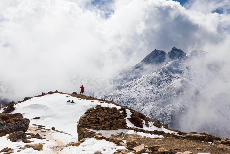 供以人员剪影常设雪山边缘拍摄的landsca 免版税库存照片