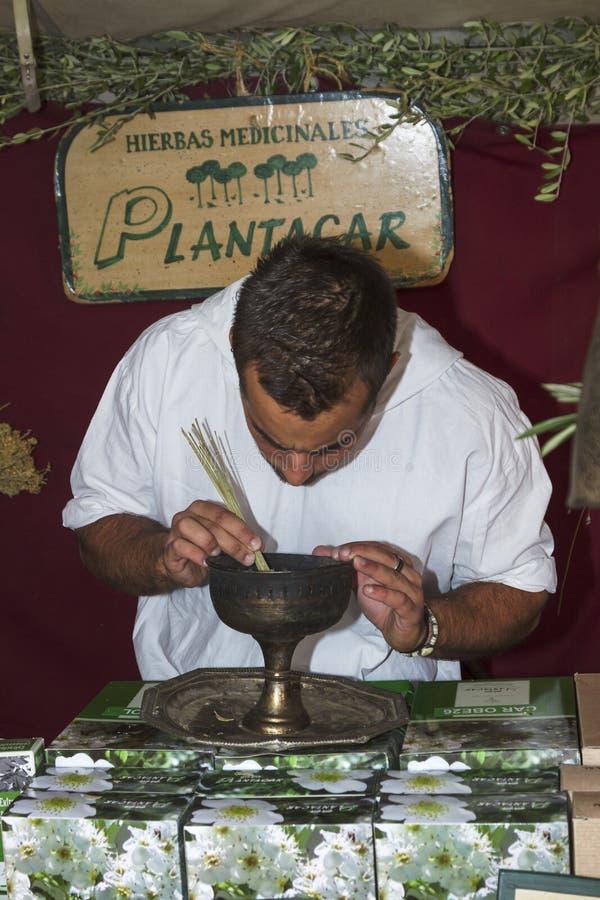 供以人员卖医药草本在à 维拉的中世纪市场上 库存照片