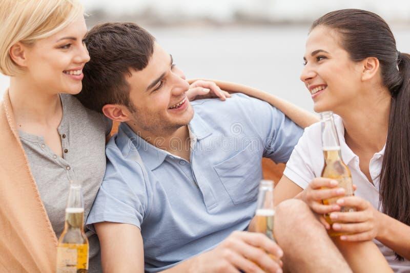 供以人员和放松在海滩的两名妇女用啤酒 免版税库存图片