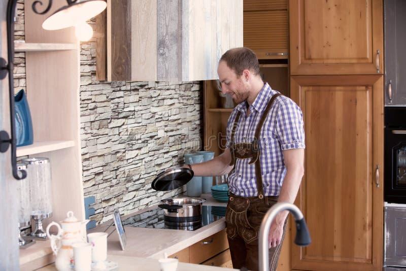 供以人员在传统巴伐利亚人衣裳standng在厨房里 库存照片