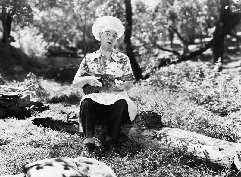 供以人员在厨师帽子坐外部和播放yukalalee (所有人被描述不更长生存,并且庄园不存在 Su 免版税库存图片