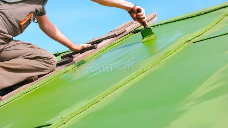 供以人员在屋顶上的掠过的绿色油漆 库存照片