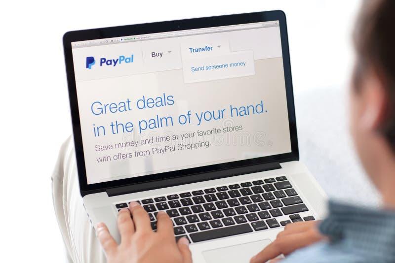供以人员在有站点的PayPal MacBook视网膜坐屏幕 免版税库存图片