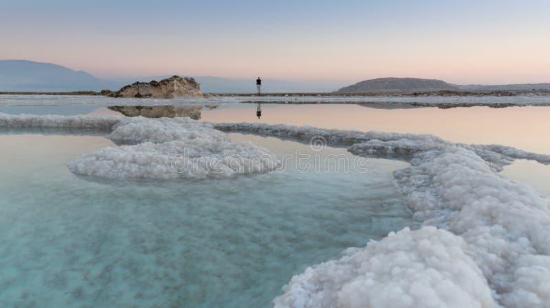 供以人员在盐丝带的身分在死海在与反射的日落在它的玻璃状镇静表面 库存照片