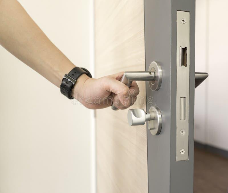 供以人员在门木头的抓住门把手不锈钢打开 免版税库存照片
