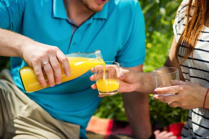 供以人员在玻璃的倾吐的汁液少妇的,野餐夏天概念 库存图片