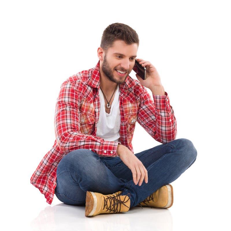 供以人员坐与盘的腿和谈话在电话 免版税库存图片