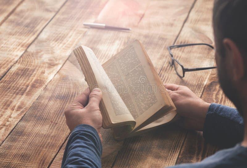 供以人员坐在一张木桌上的阅读书 图库摄影