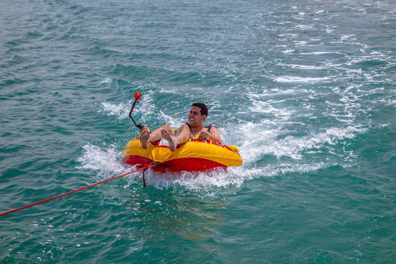 供以人员坐在一条小船拖曳的可膨胀的圆环在水中和 库存图片