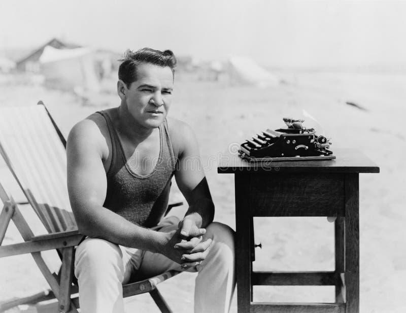 供以人员坐在与他的打字机的海滩(所有人被描述不更长生存,并且庄园不存在 供应商warrantie 免版税图库摄影