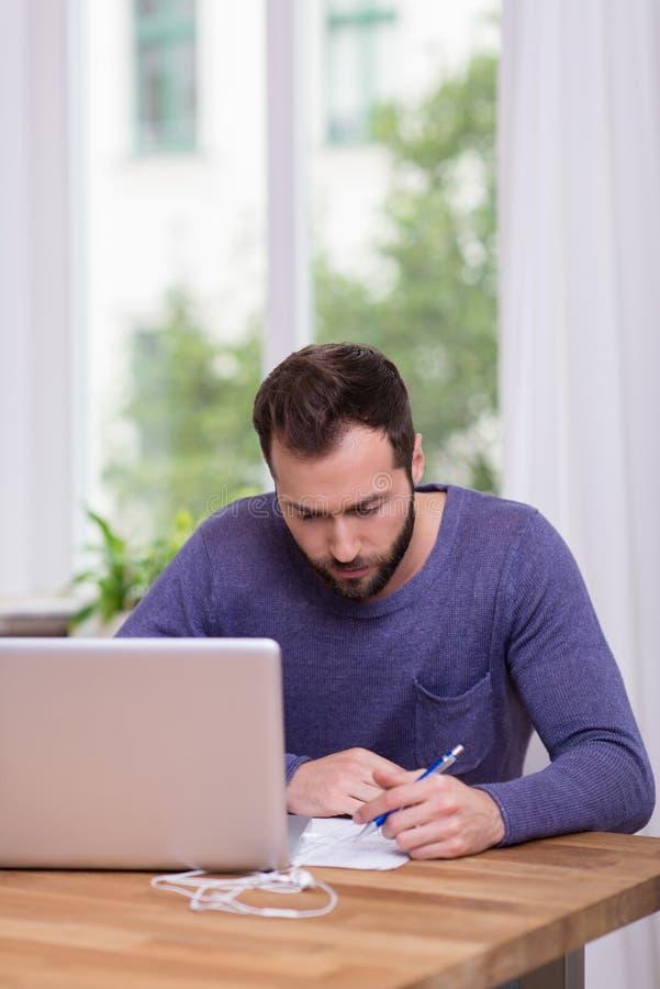 供以人员坐在运作在他的办公室的桌上 免版税库存照片